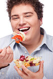 Chubby man with fresh salad. Happy young chubby man eating fresh salad with fork, isolate on white stock images