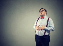 Chubby man having indigestion problem. Irritated man with overweight wearing glasses and formal clothing having digestive trouble Royalty Free Stock Photography