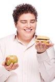 Chubby man holding apple and hamburger Stock Photography
