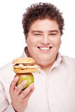 Chubby man holding apple and hamburger Royalty Free Stock Image
