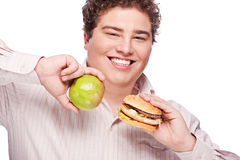 Chubby man holding apple and hamburger Royalty Free Stock Photography