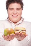 Chubby man holding apple and hamburger Royalty Free Stock Images