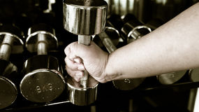 Chubby man holding 5 kg rustic dumbell Royalty Free Stock Photos