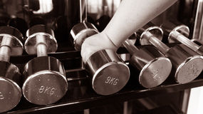 Chubby man holding rustic dumbell copper black and white Stock Image