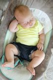 Chubby Newborn Baby Girl Sleeping in Infant Swing. A cute, chubby little newborn baby girl is sleeping in her infant swing at home. Soft focus royalty free stock photos