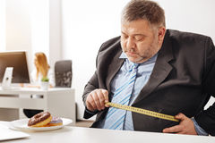 Chubby office worker having concerns about his weight Royalty Free Stock Photos