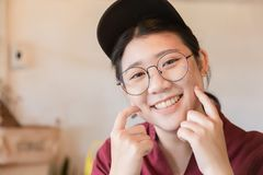 Chubby plump teen cute white tooth smile Asian young student with glasses. And hat finger touch cheek with copy space royalty free stock image
