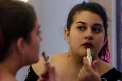 Chubby woman putting on some makeup. Chubby woman putting on makeup, makeup in front of the mirror stock image