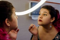 Chubby woman putting on some makeup. Chubby woman putting on makeup, makeup in front of the mirror stock photography