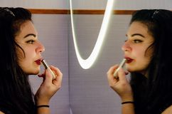 Chubby woman putting on some makeup. Chubby woman putting on makeup, makeup in front of the mirror stock photo