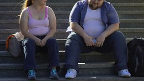 Chubby students talking and smiling, sitting on stairs near university, friends stock video