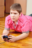 Chubby teenage boy playing computer games. Using game controller Royalty Free Stock Photography