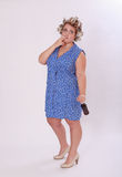 Chubby Woman com o encrespador de cabelo que fuma um cigarro Imagem de Stock