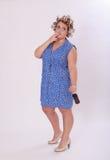 Chubby Woman con il bigodino di capelli che fuma una sigaretta Immagine Stock