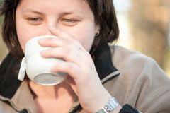 Chubby woman drinking from a camping plastic mug royalty free stock photos