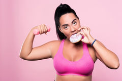 Chubby woman eating donut while exercising Royalty Free Stock Images