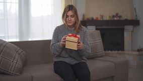 Chubby woman find gift which was left for her on sofa. Plump girl opening box with red ribbon and surprised by what`s stock video