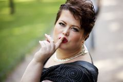 Chubby woman hush. Chubby woman with finger on her lips gesturing for quiet royalty free stock photography