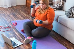 Chubby woman sport at home sitting lifting dumbbells watching video concentrated stock images