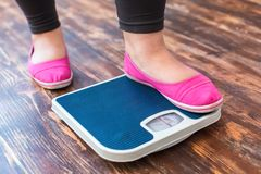 Chubby woman sport at home standing on scales checking weight close-up
