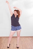 Chubby woman with stretched your arms up. Chubby woman with red hair stretched her arms above her head - Studio Shot royalty free stock photography