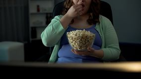 Chubby woman taking handful of popcorn and eating in front of TV, laziness. Stock photo stock image