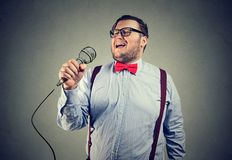 Chubby young man singing expressively. Young chubby man in formal outfit and eyeglasses singing with deep emotions Stock Photos