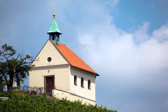 Chuch with crucifix on steeple. Prague chuch with crucifix on a patina (copper) steeple Royalty Free Stock Image