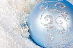Chuchería azul blanda de la Navidad encendido a la nieve. Fotografía de archivo