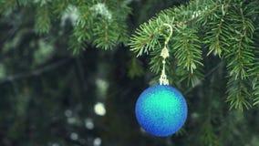 Chuchería azul de la Navidad que cuelga en árbol de abeto nevoso almacen de metraje de vídeo