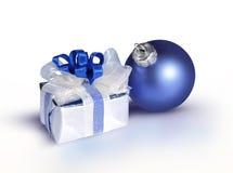 Chuchería azul y un regalo en un fondo blanco Imagen de archivo libre de regalías