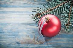 Chuchería brillante roja de la rama del pino en las celebraciones del tablero de madera concentradas Imagen de archivo libre de regalías