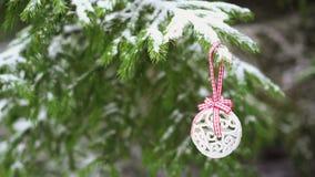Chuchería de la decoración de la Navidad que cuelga en árbol de abeto nevoso almacen de metraje de vídeo