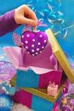 Chuchería de la Navidad de la dimensión de una variable del corazón en mano del niño Imagen de archivo libre de regalías