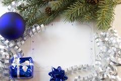 Chuchería de la tarjeta de Navidad y ramificación azules del abeto Imágenes de archivo libres de regalías