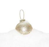 Chuchería del Año Nuevo de la Navidad del oro, bola que miente en la nieve blanca Foto de archivo libre de regalías