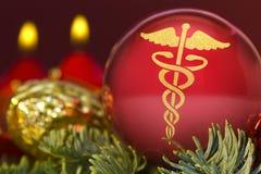 Chuchería roja con la forma de oro de un símbolo del asclepius serie Foto de archivo libre de regalías