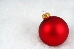 Chuchería roja de la Navidad en la nieve Fotos de archivo libres de regalías