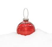 Chuchería roja del Año Nuevo de la Navidad, bola que miente en la nieve blanca Fotos de archivo