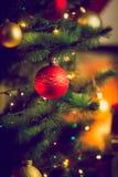 Chuchería roja en el árbol de navidad al lado de la chimenea en la sala de estar Fotografía de archivo