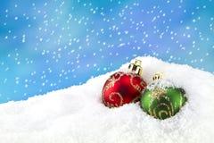 Chuchería verde y roja de la Navidad en la nieve imágenes de archivo libres de regalías