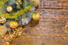 Chucherías coloridas de la Navidad del oro en pino Fotografía de archivo