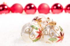 Chucherías de cristal blancas y chucherías rojas en nieve Fotografía de archivo libre de regalías