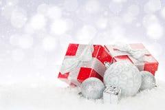 Chucherías de la Navidad y cajas de regalo rojas sobre fondo del bokeh de la nieve Fotografía de archivo libre de regalías