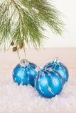 Chucherías de la Navidad y rama de árbol azules de pino Foto de archivo libre de regalías