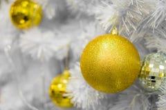 Chucherías de oro de la Navidad en las ramas blancas Fotos de archivo libres de regalías