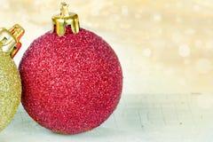 Chucherías de oro y rojas de la Navidad Imagenes de archivo