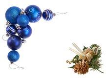 Chucherías decorativas de la Navidad azul y cono de oro del pino que forman un marco del día de fiesta Foto de archivo libre de regalías