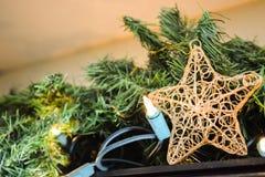 Chucherías del Año Nuevo de las decoraciones de la estrella del árbol de navidad encendido adornadas con el fondo borroso Imagenes de archivo