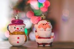 Chucherías del muñeco de nieve y de Papá Noel con las luces de la Navidad en el fondo Fotos de archivo
